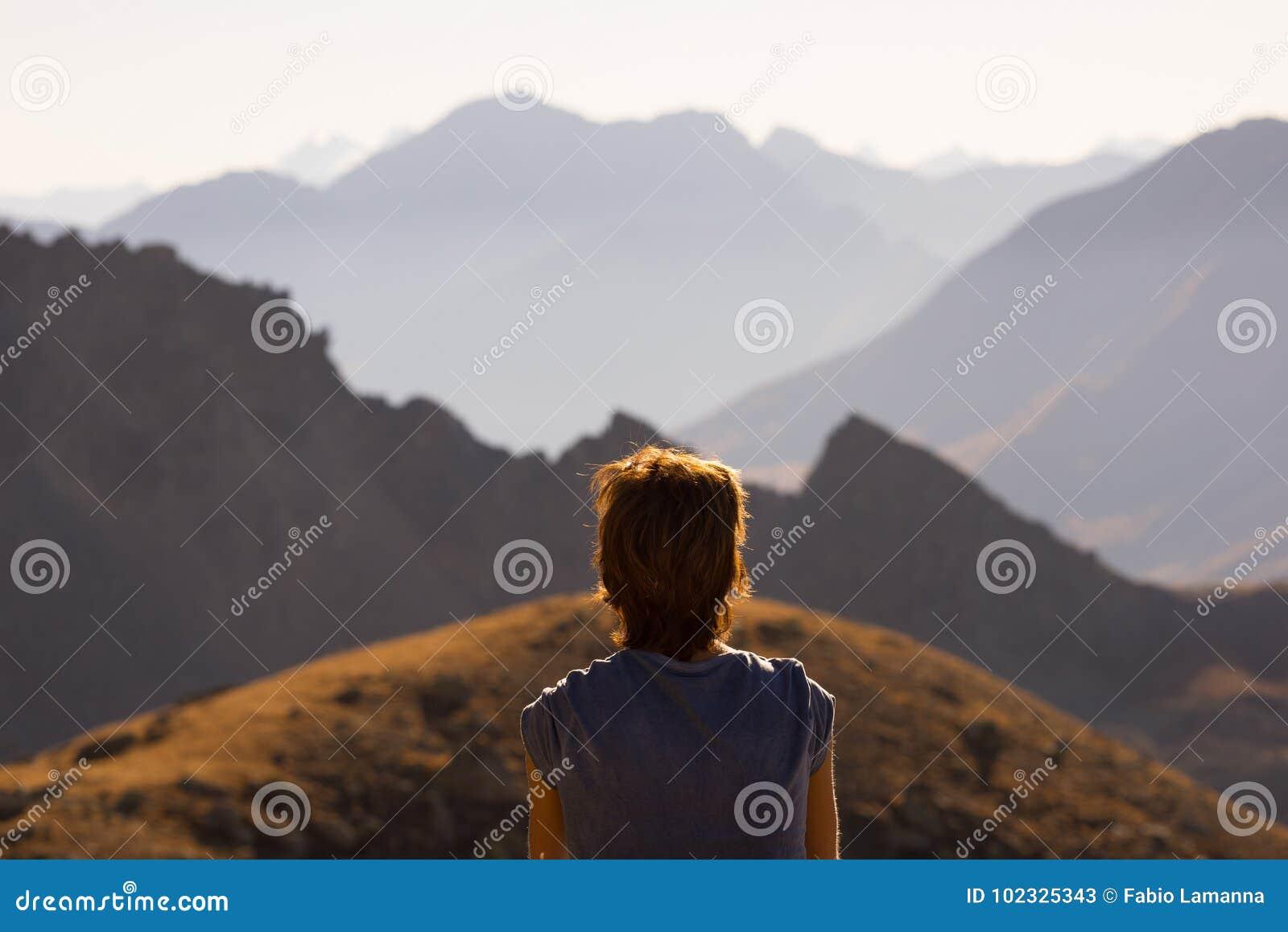 En person som ser sikten som är hög upp på fjällängarna Expasive landskap, idyllisk sikt på solnedgången isolated rear view white