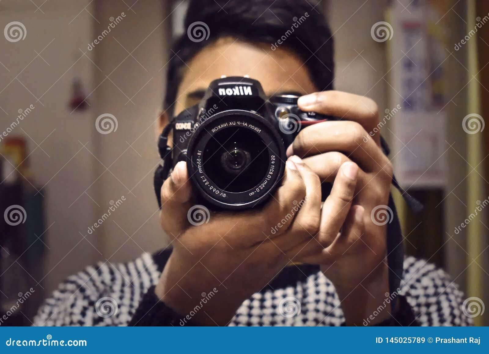 En person som tar fotoet från hans Nikon DSLR kamera som vänder mot kameran