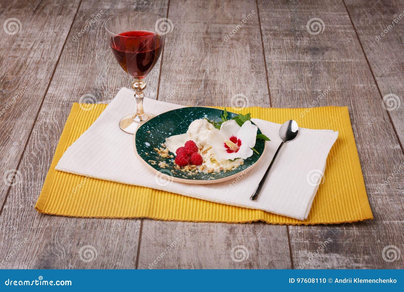 En platta av glass med bär och den dekorativa blomman Röd fruktfruktsaft och vitglass på en träbakgrund