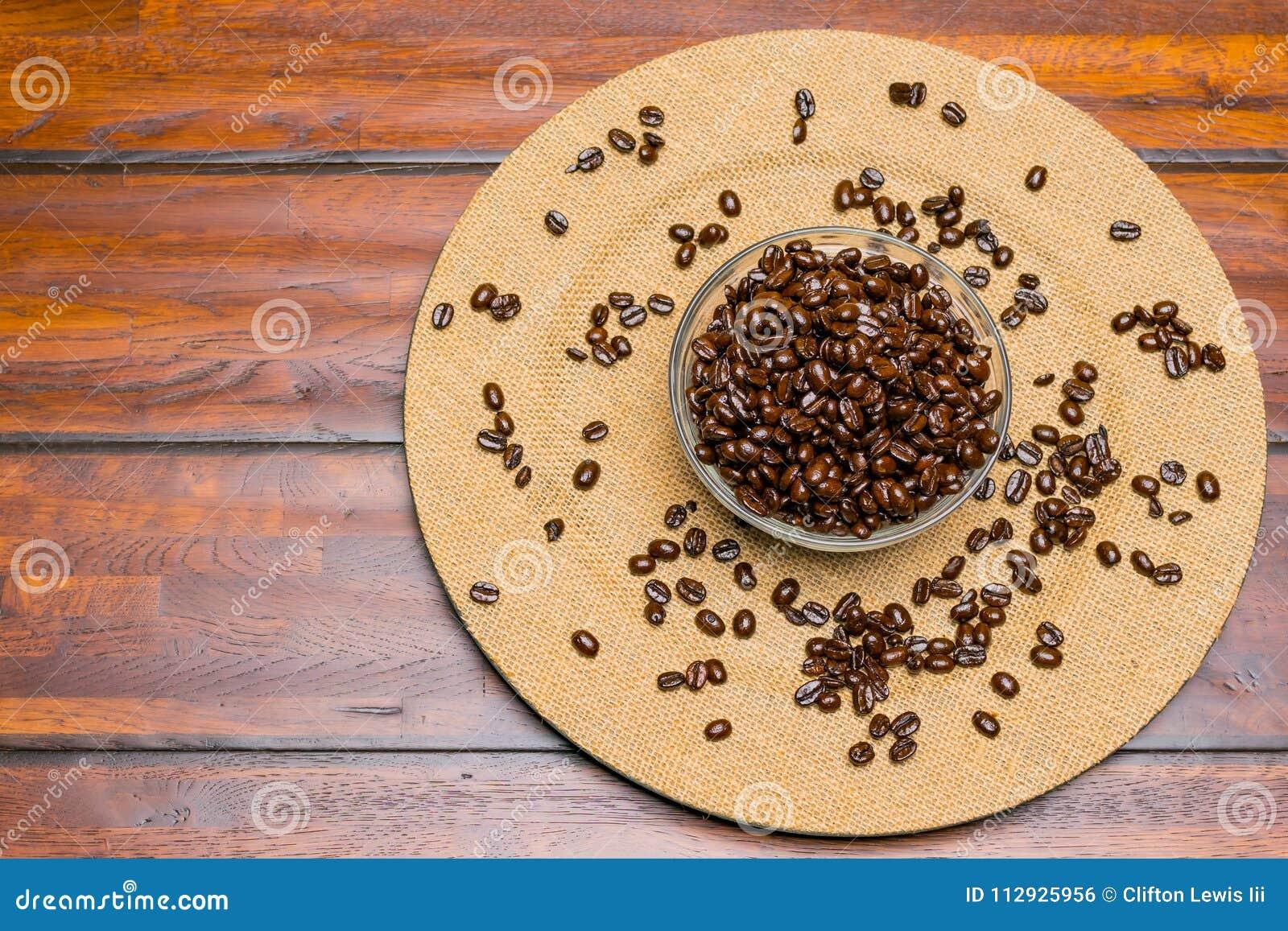 En platta av hela kaffebönor på en träbakgrund