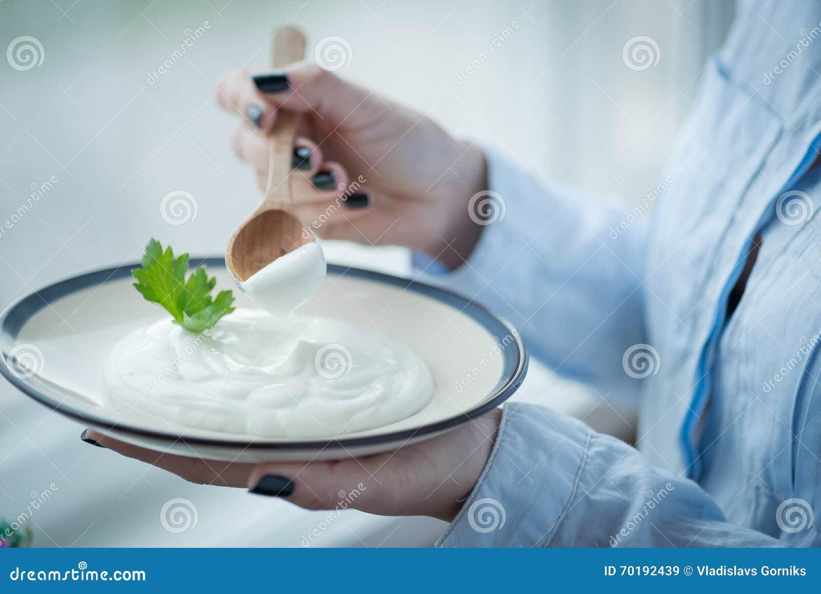 En platta med ny yoghurt i kvinnas händer