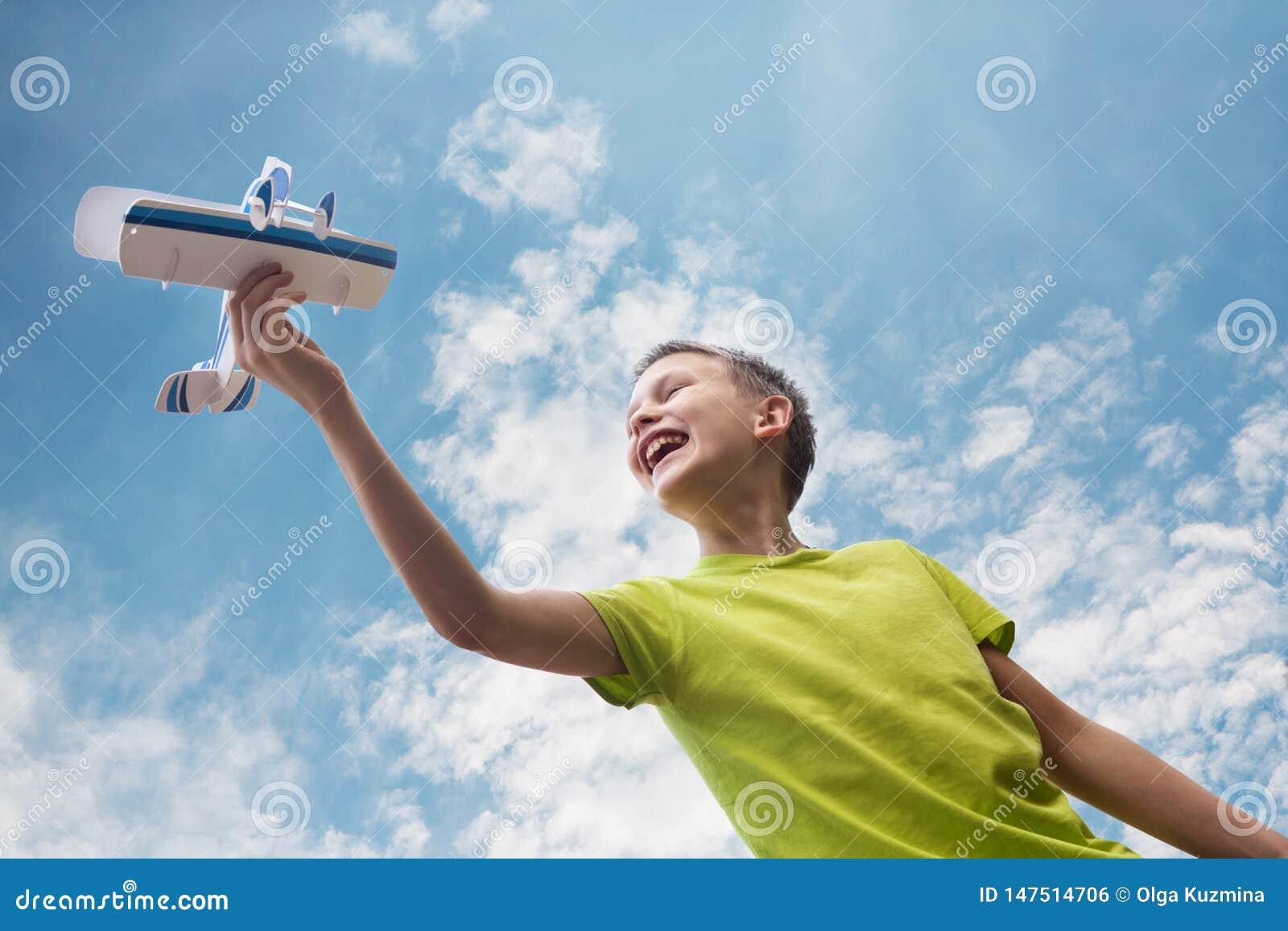 En pojke av det europeiska utseendet med ett flygplan mot himlen med moln Ljusa sinnesr?relser Kopiera utrymme