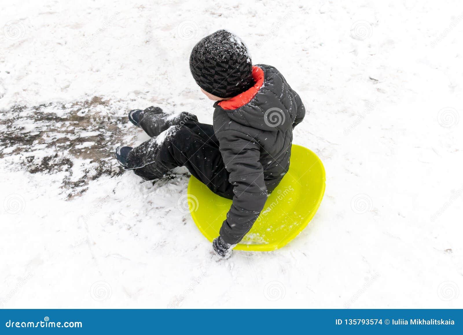En pojke av sju gamla år rider glidbanan, ner kullen på den gröna issläden Begrepp av vinteraktiviteter, rekreation och barn