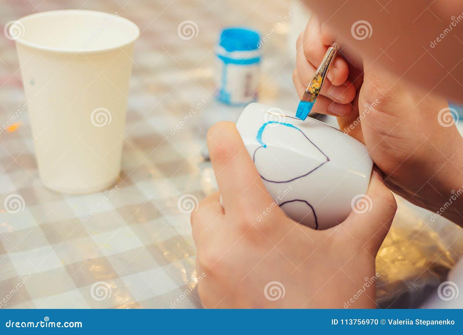 En pojke drar en hjärta på den vita koppen med en blå målarfärg