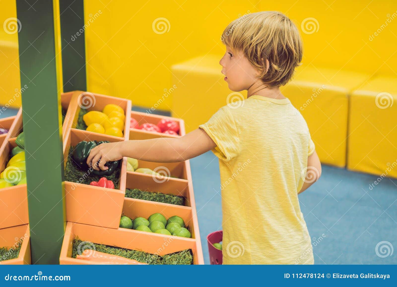 En pojke köper leksakgrönsaker i en leksaksupermarket