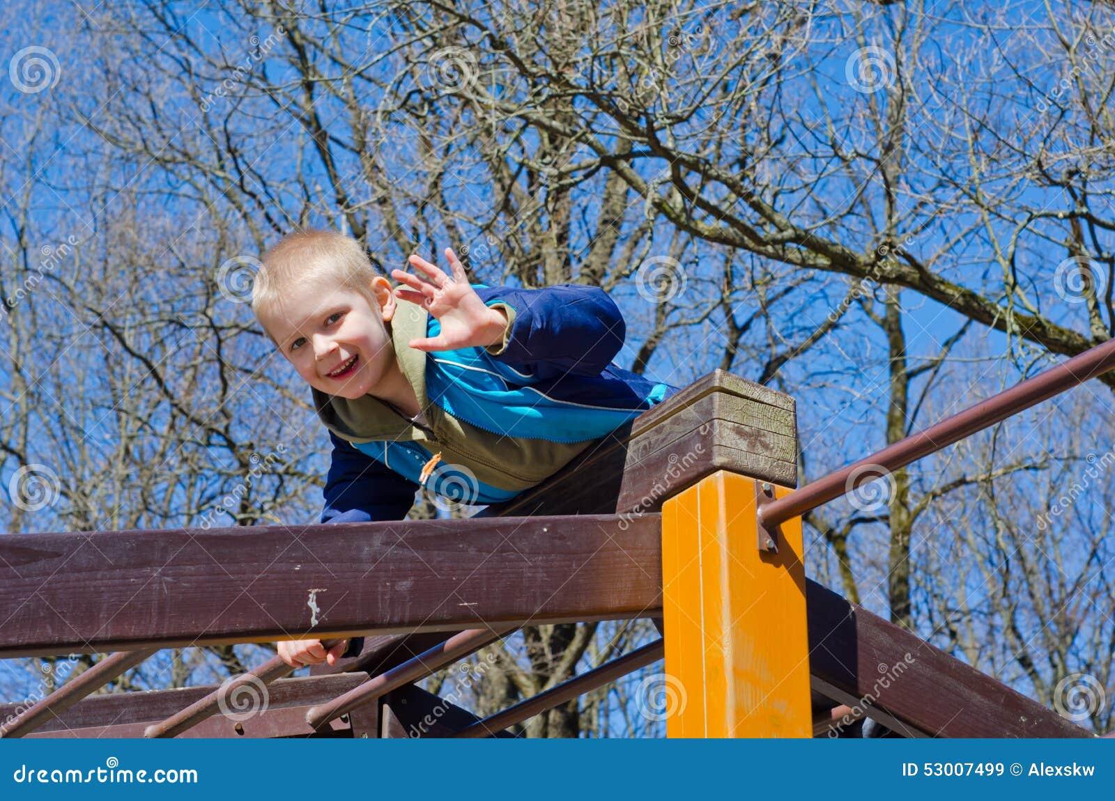 En pojke klättrar på lekplats