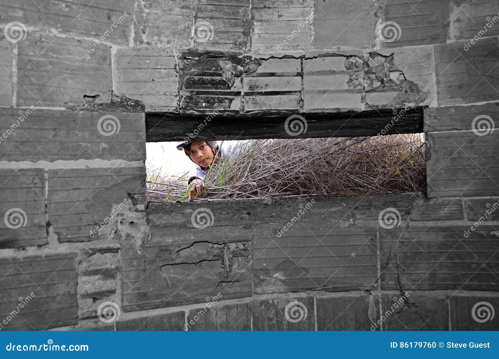 En pojke som ser in i en bunker för världskrig två
