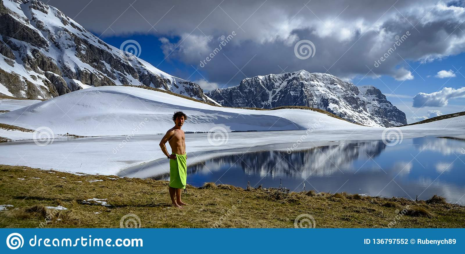 En pojke står bredvid bergsjön framme av snöberg i den soliga och molniga dagen