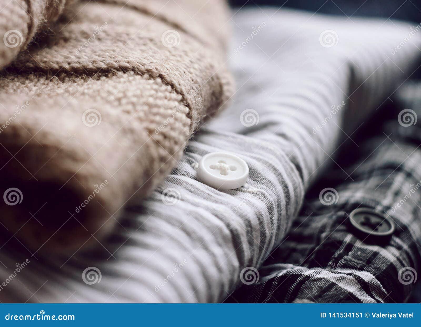 En proper bunt av kläder - en beige halsduk och två skjortor