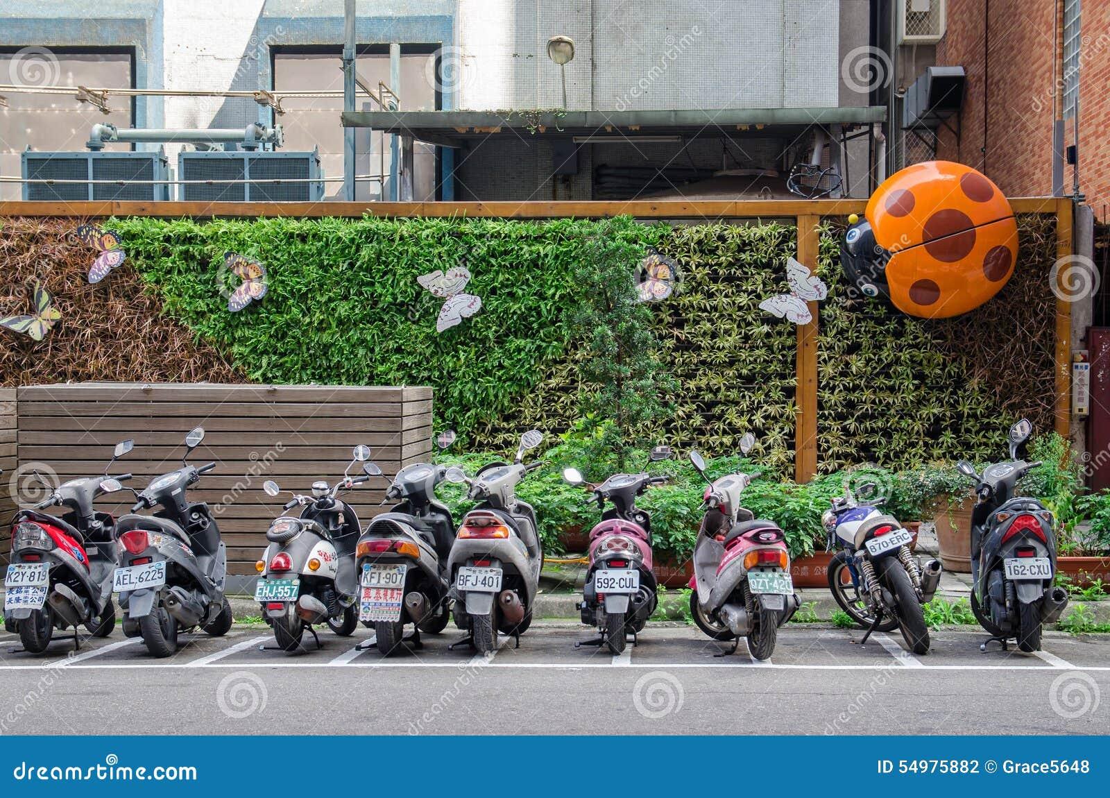 En rad av motorcykelparkering längs vägrenen i Taipeis gata