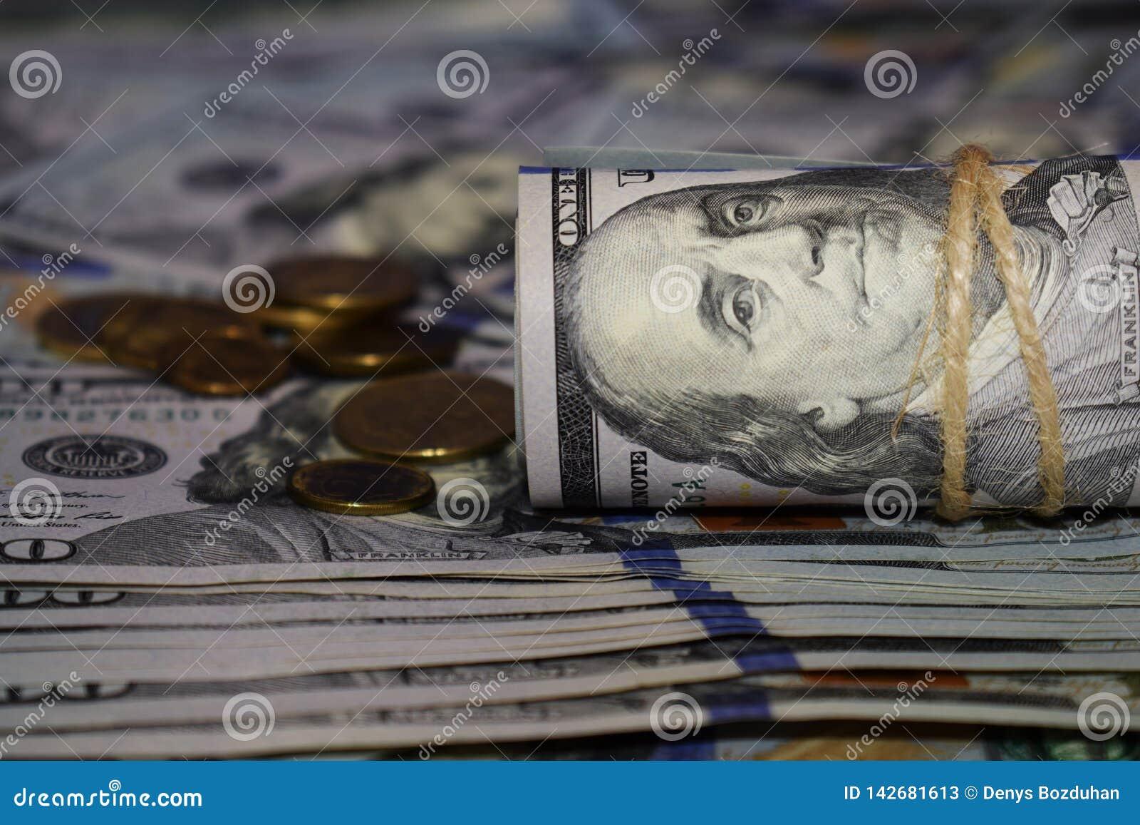 En rulle av dollar på bakgrunden av spritt hundra dollarräkningar och olika mynt