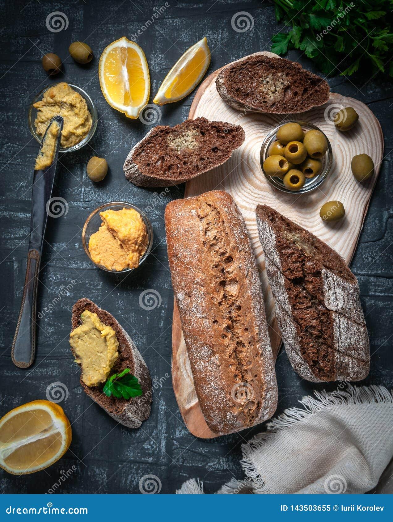 En sammansättning av två bagetter av kli och helt kornmjöl Smörgås av hummusen och oliv På trämellanrummet Sikt från