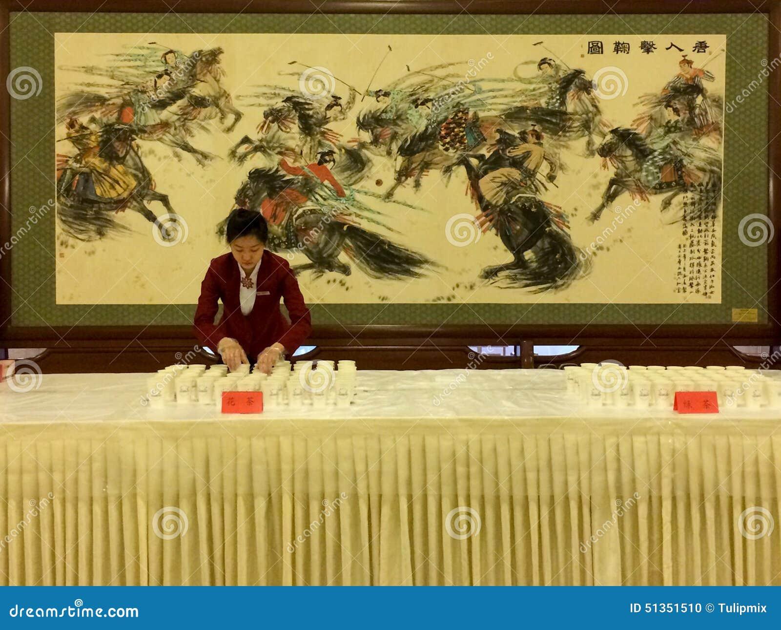 En servitris förbereder sig att tjäna som te i den stora Hallen av folk i Peking