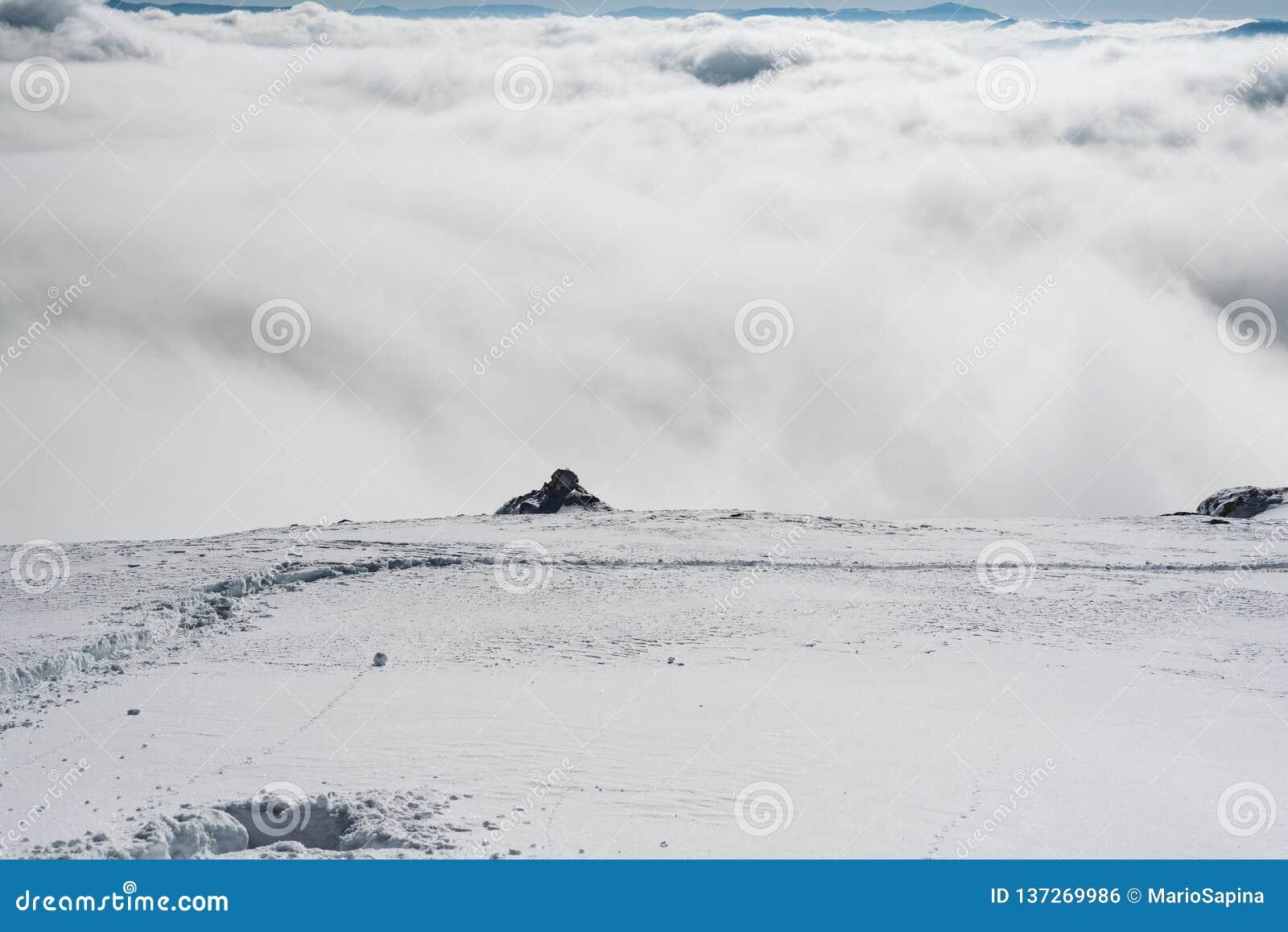 En sikt av dalen från kanten av en snöig lutning