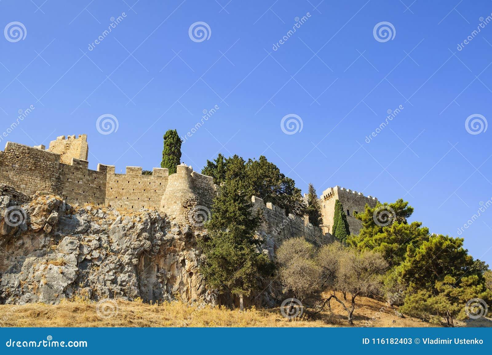 En sikt av de forntida väggarna och tornen av akropolen av Lindos Rhodes ö, Grekland