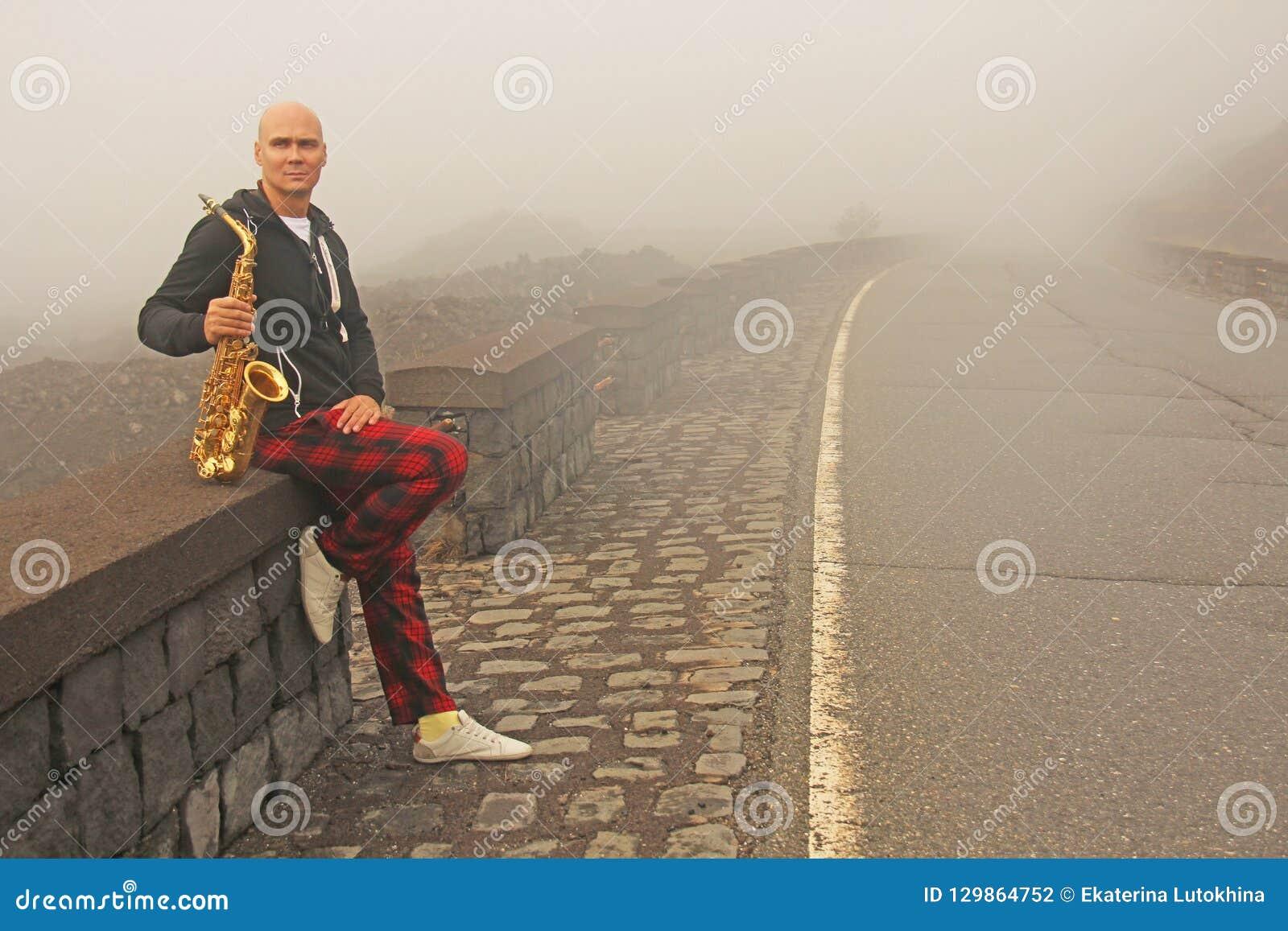 En skallig man spelar på en guld- alt- saxofon på vägrenen, igen
