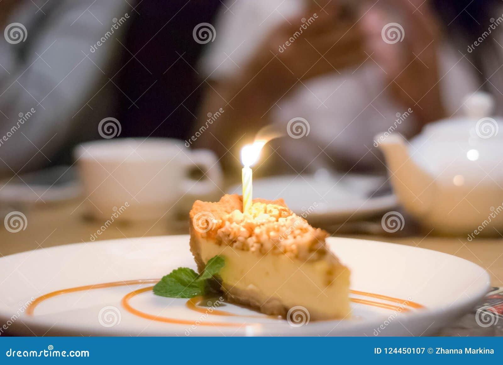En skiva av ostkaka med en brinnande stearinljus för en födelsedag