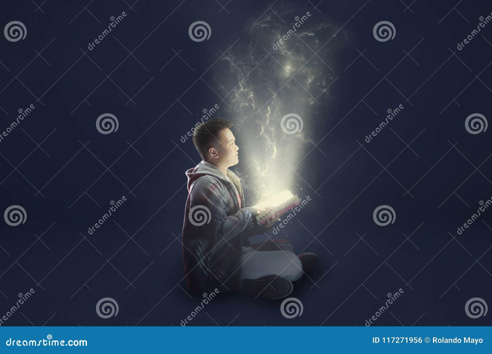 En skolapojke som bär ett omslagsinnehav och läsning en magisk bok med mystiskt ljust kommande ut Idéer från läsning Visa edu