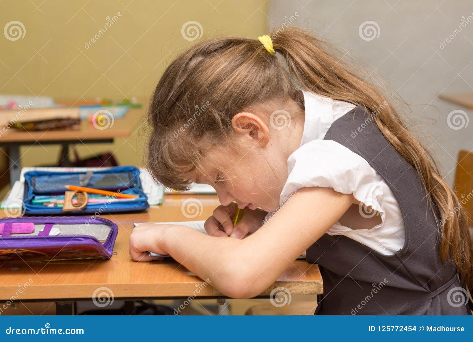 En skolflicka med en fel ställing på kursen skriver i en anteckningsbok