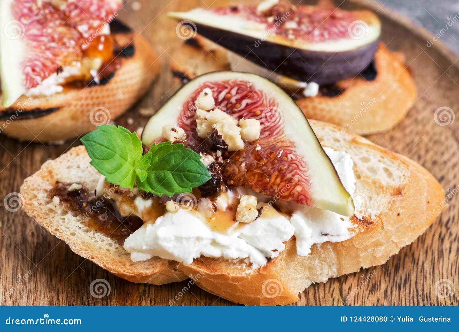 En smörgås med fikonträd, ost, muttrar och honung Selektiv fokus, närbild
