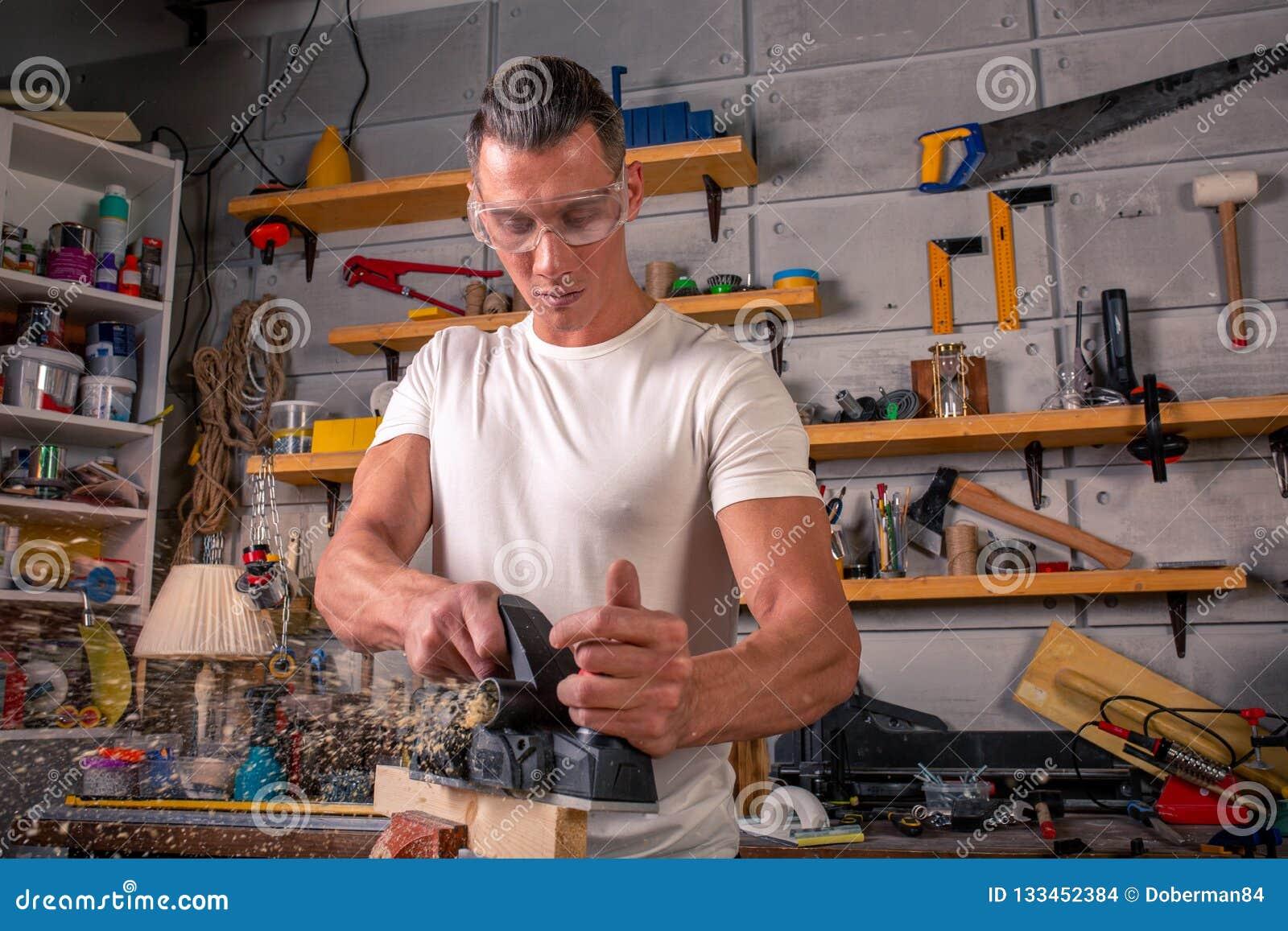 En snickare arbetar på snickeri maskinhjälpmedlet Sågmöblemangdetaljer med en cirkelsåg Process av att såga delar