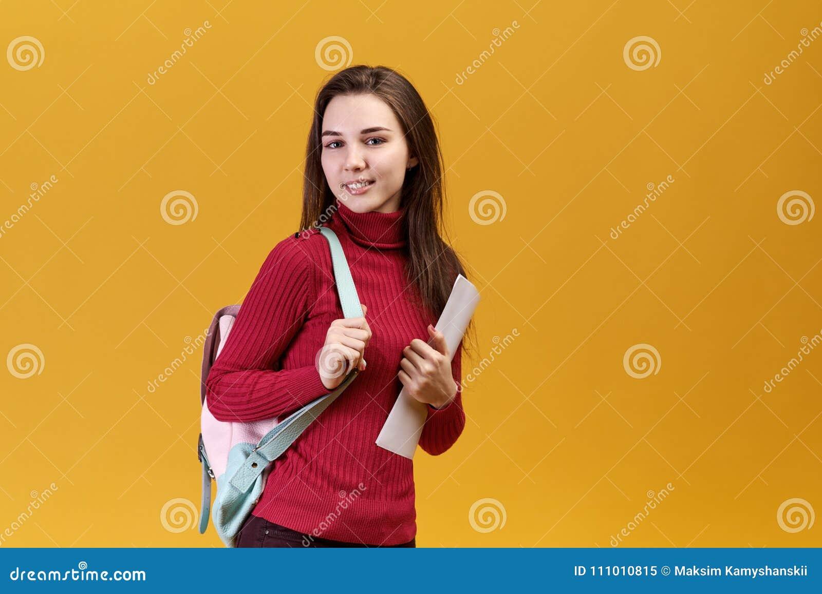 En snygg kvinna har ett glat uttryck, ser högra glänsande gråa ögon på dig och att bära en röd tröja