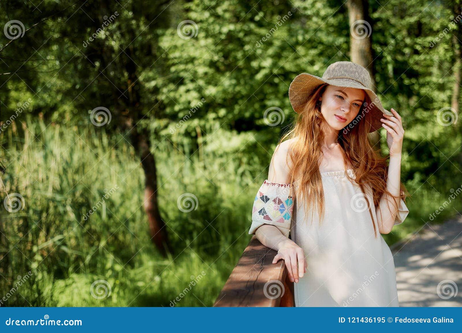 En sofistikerad rödhårig flicka i en enkel linneklänning, i en ljus bredbrättad hatt se modellen naturlig skönhet