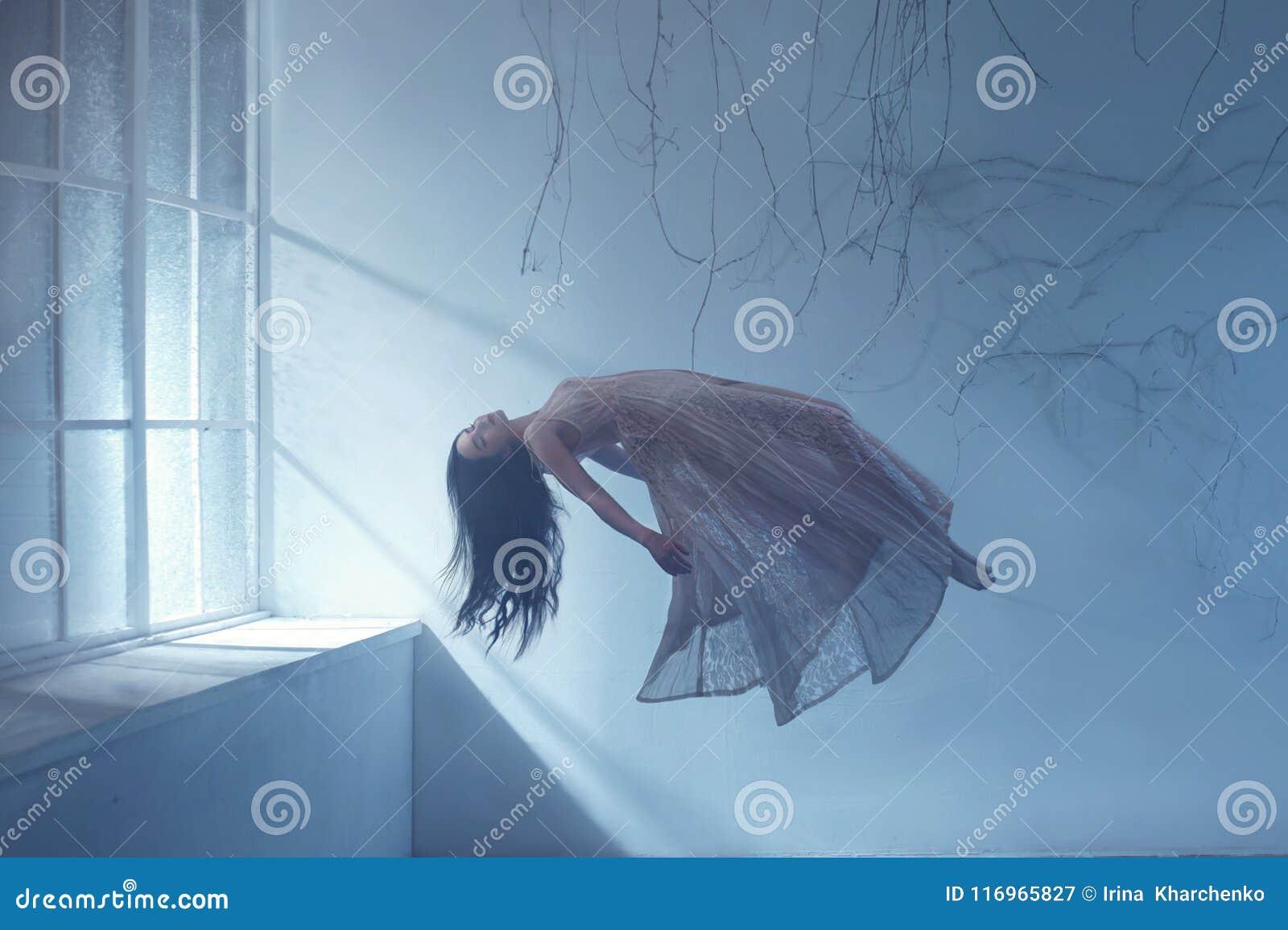 En spökeflicka med långt hår i en tappningklänning Ett fotografi av svävning som liknar en dröm Ett mörkt gotiskt rum med