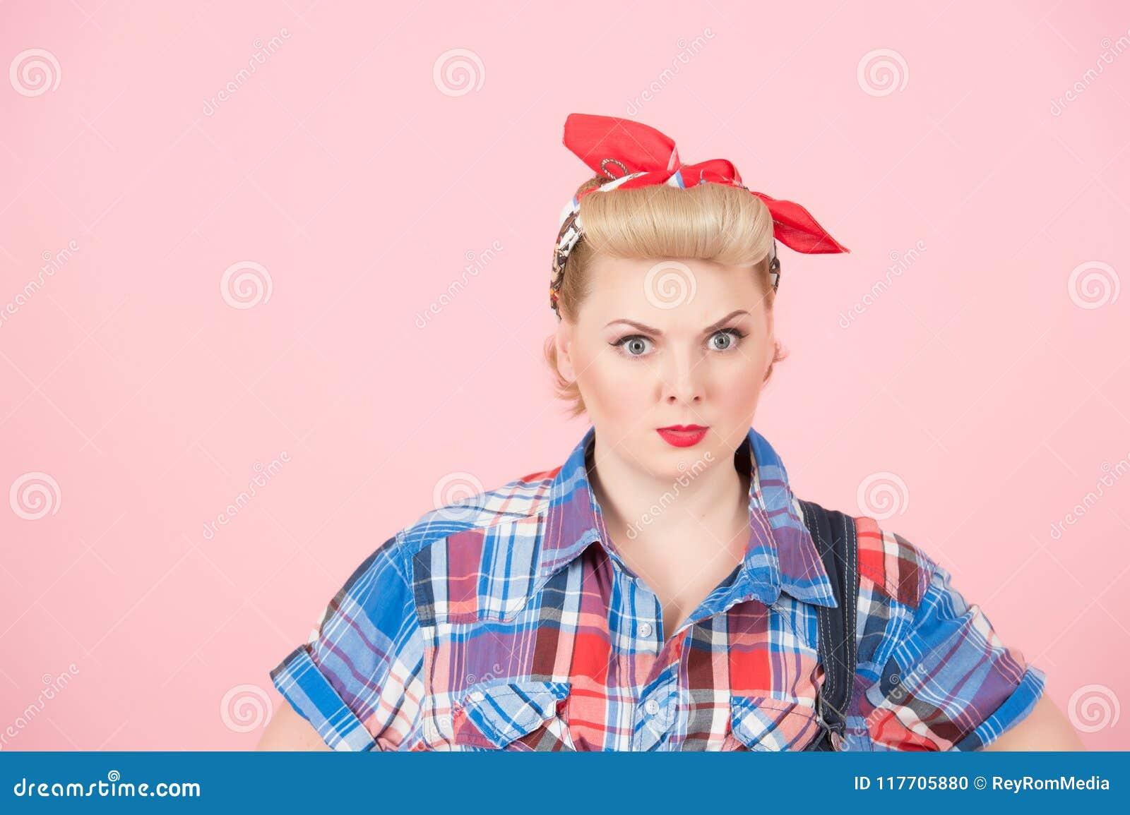 En stående av den blonda krullningsutvikningsflickan med den röda head halsduken Stilfullt härligt smink på rosa bakgrund Koncent