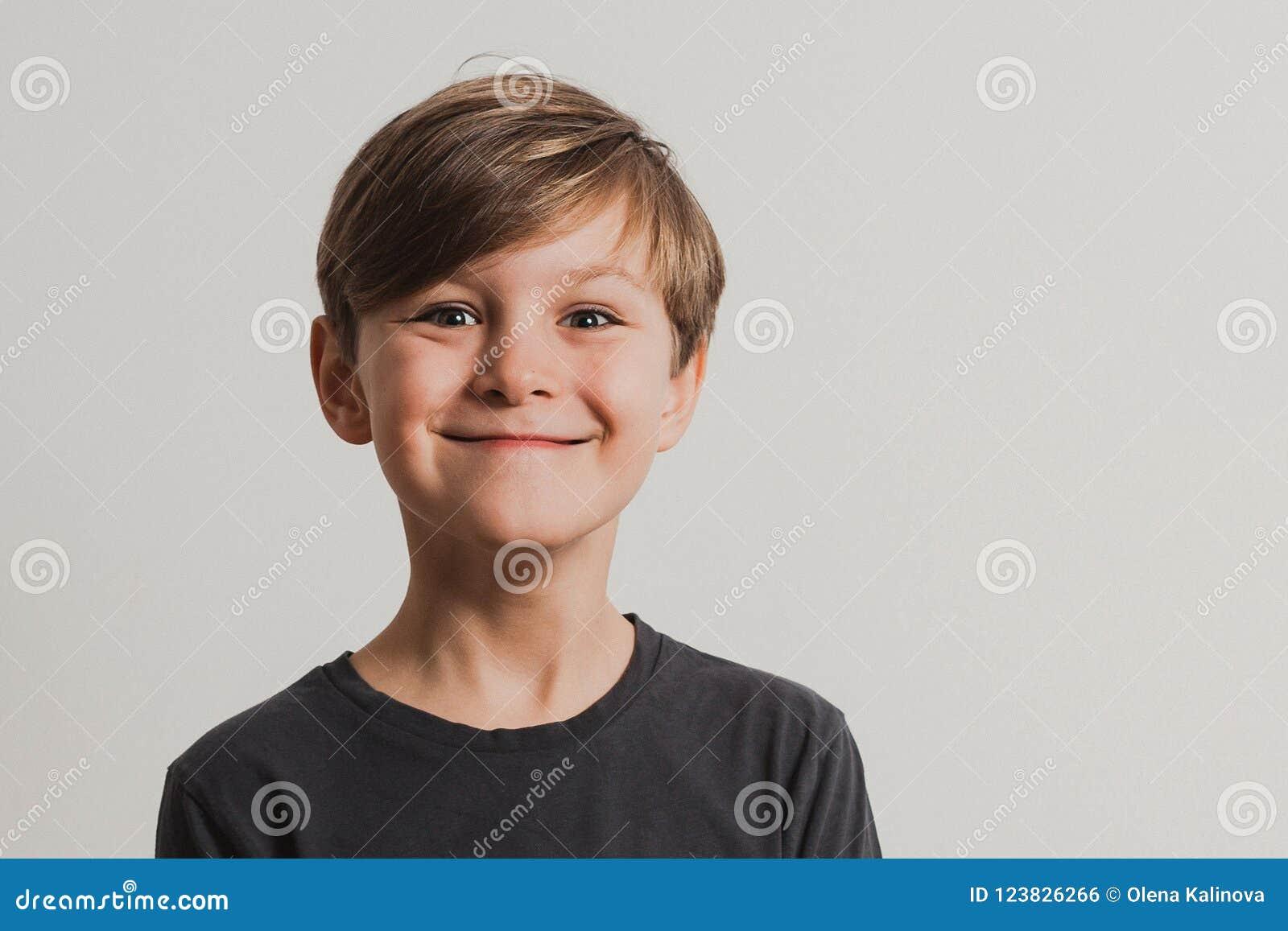 En stående av den gulliga pojken som drar framsidor