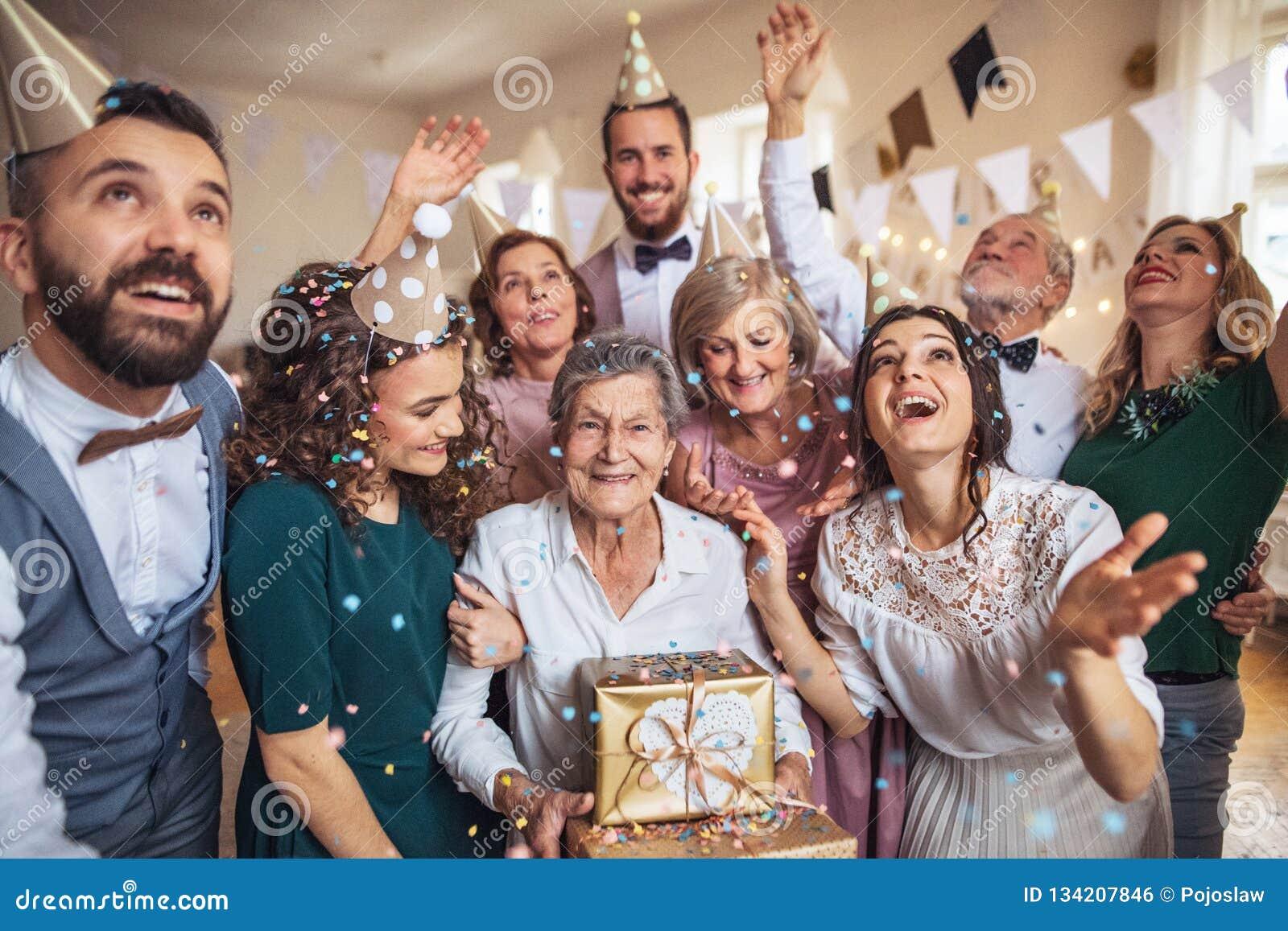 En stående av den multigeneration familjen med gåvor på ett inomhus födelsedagparti