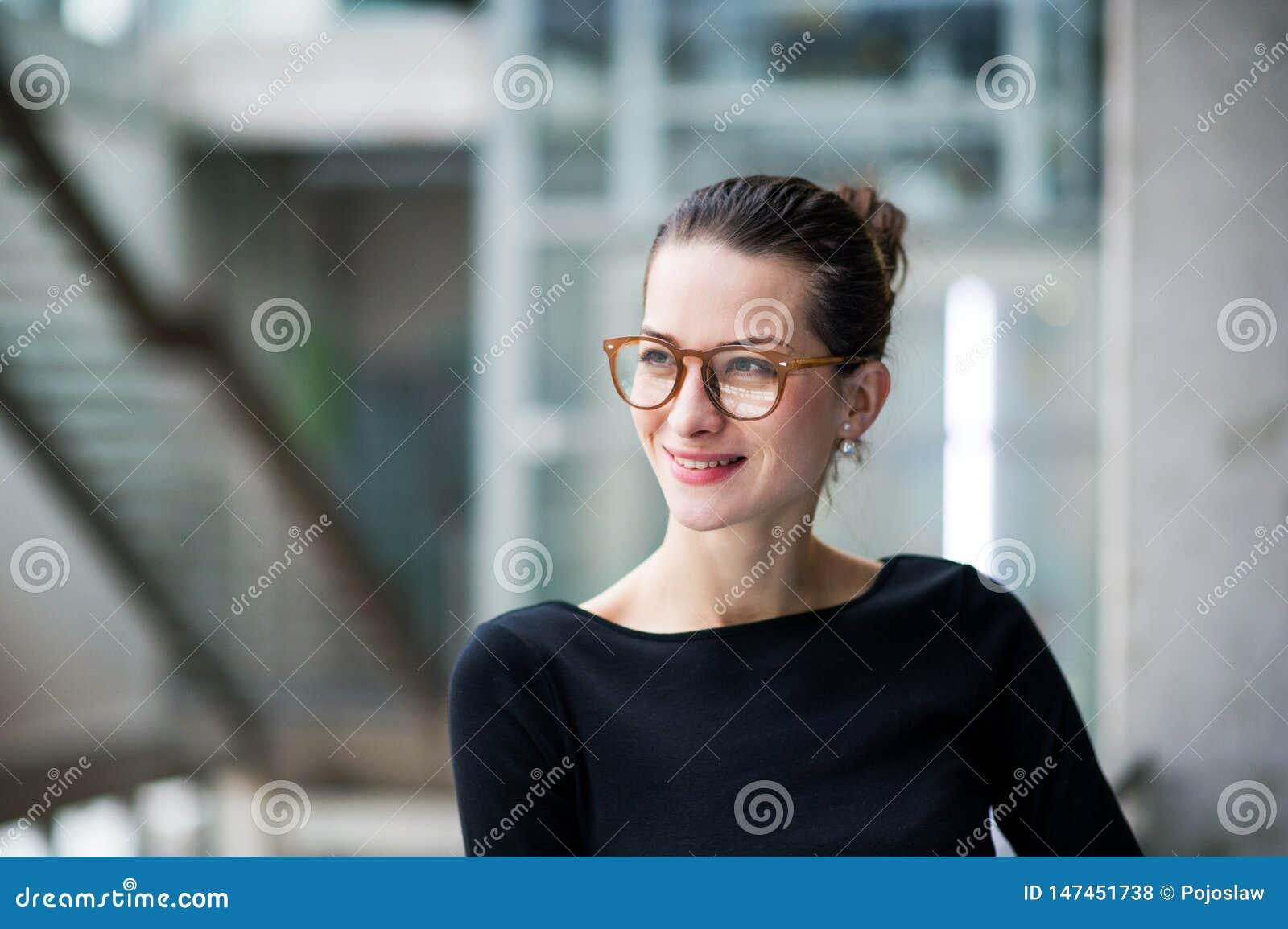 En stående av det unga affärskvinnaanseendet i korridor utanför kontor