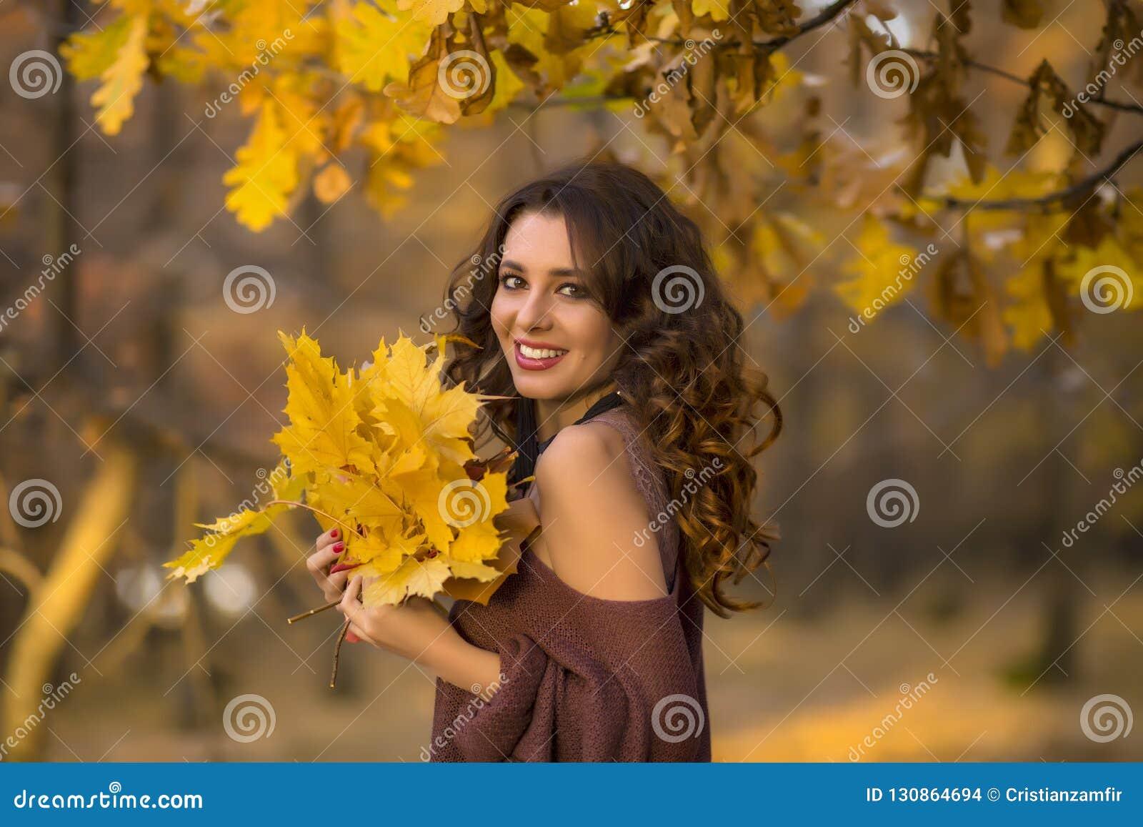 En stående av en härlig ung kvinna i en höstskog Lifes