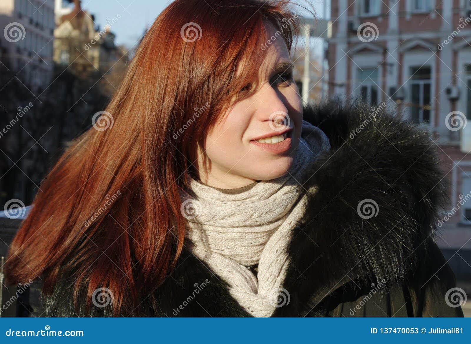 En stående av en ung flicka, som ser bort och en ljus vintersol Blickar försiktigt till sidan