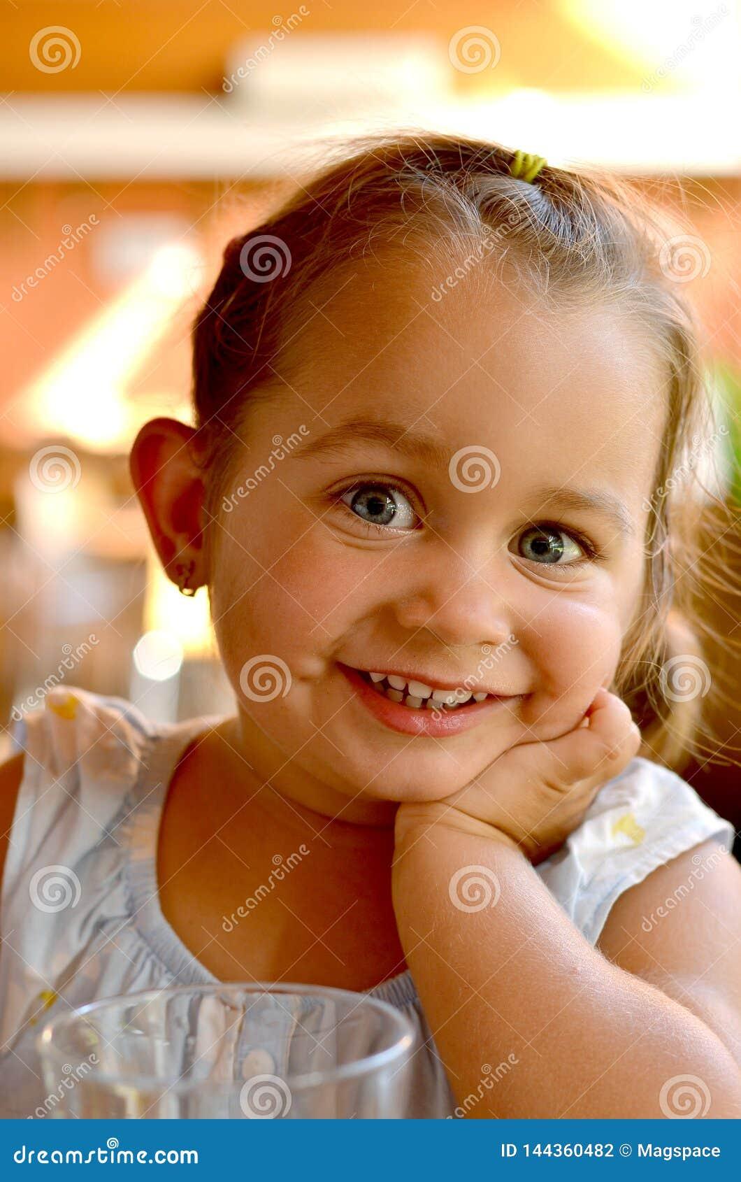 En stående av ungt le som är härligt, behandla som ett barn flickan med blont hår