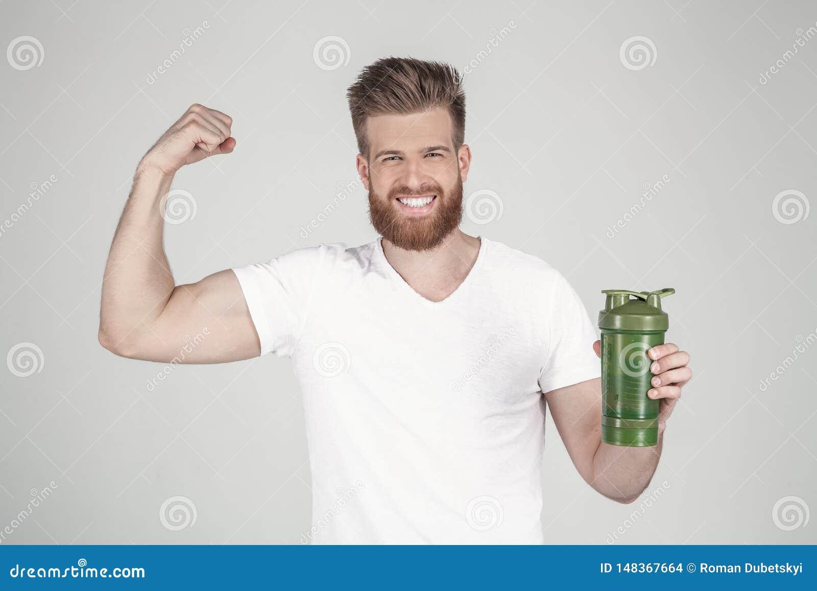 En st?ende av en h?rlig man med ett sk?gg och en trendig frisyr, ikl?dda tillf?lliga kl?der, rymmer en sportshaker och