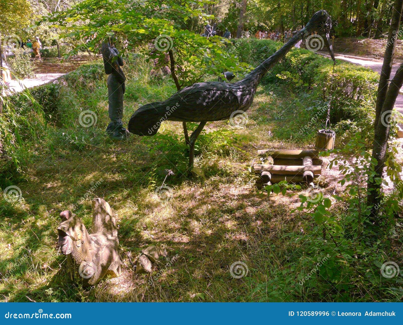 En staty av en träkran som tar en hink av vatten från brunnen Utställning i parkera