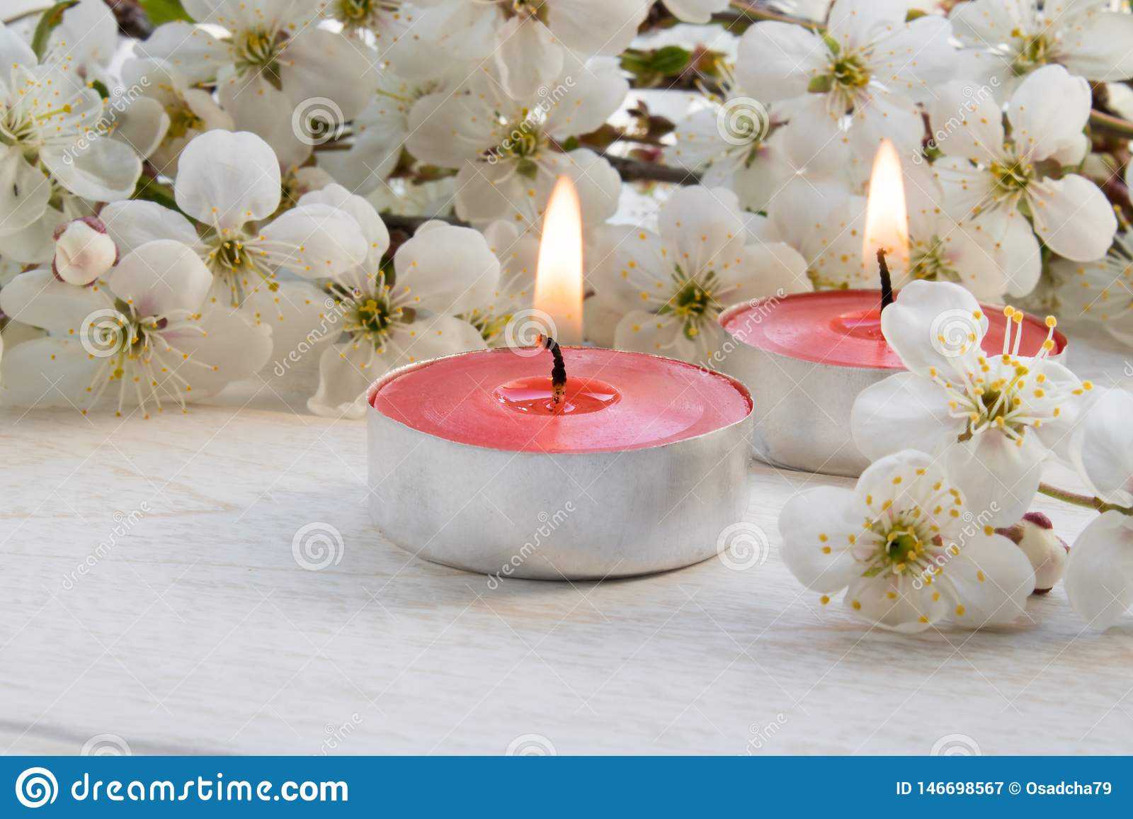 En stearinljus st?r p? en tr?vit tabell n?ra filialerna av vita blommor av k?rsb?ret