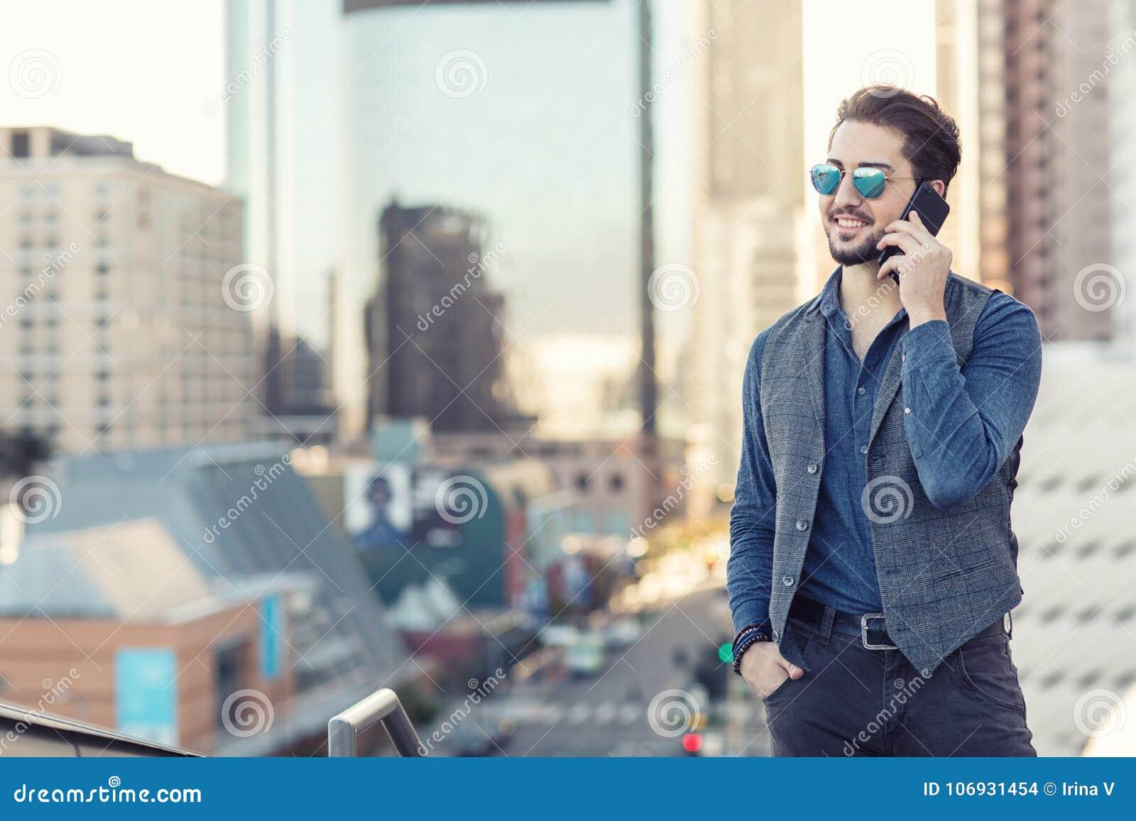 En stilig ung man som talar på telefonen i i stadens centrum Los Angele
