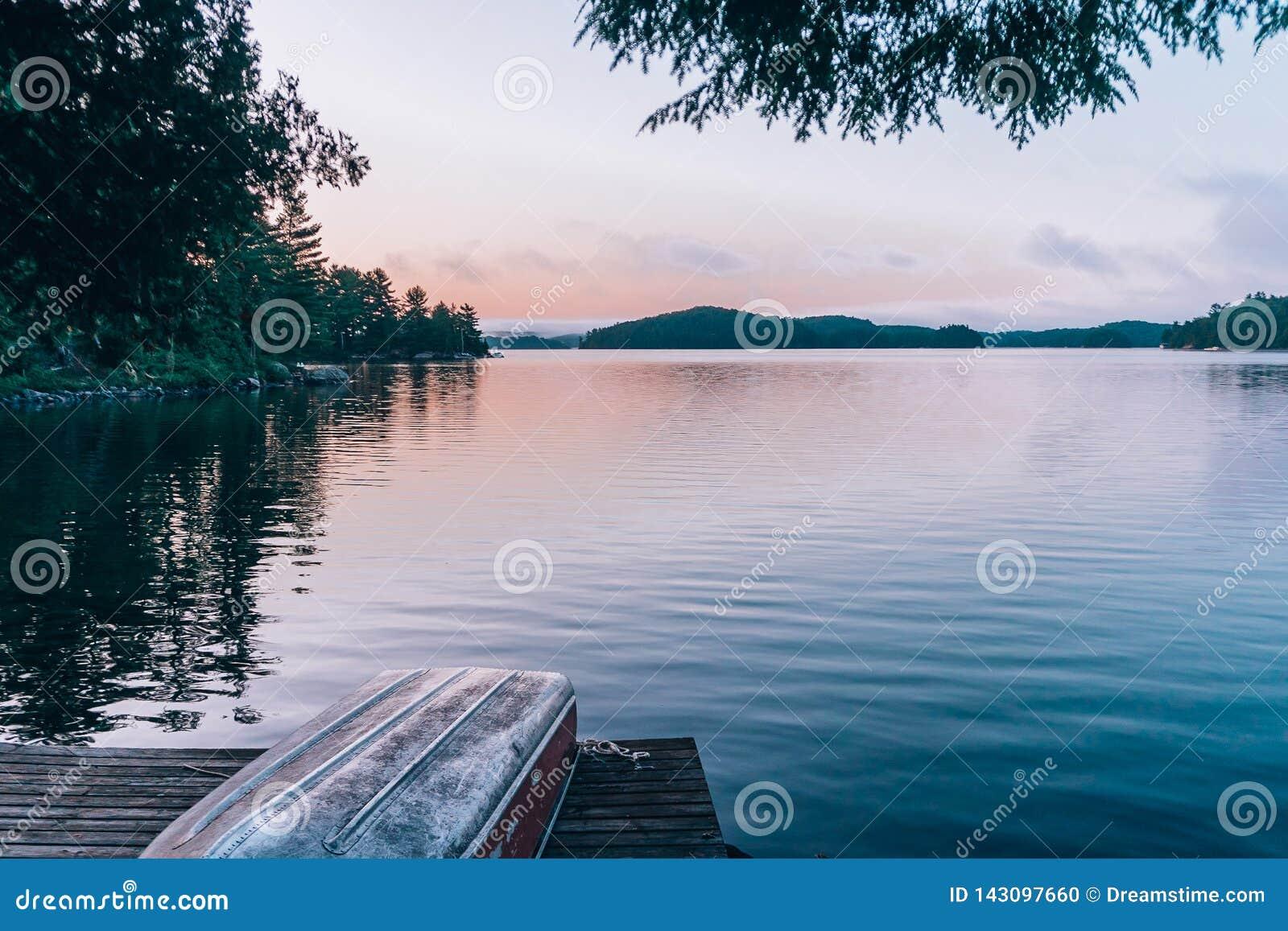En stilla sjö under solnedgång med ett fartyg på en skeppsdocka