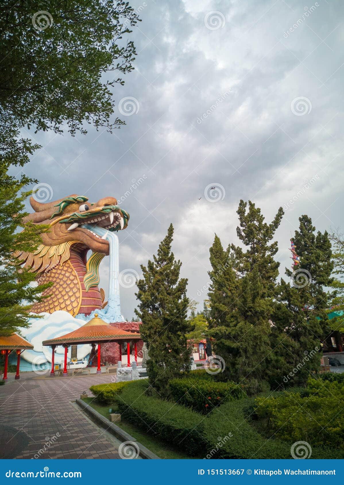 En stor drakebyggnad i trädgården, medan himlen är nära att regna