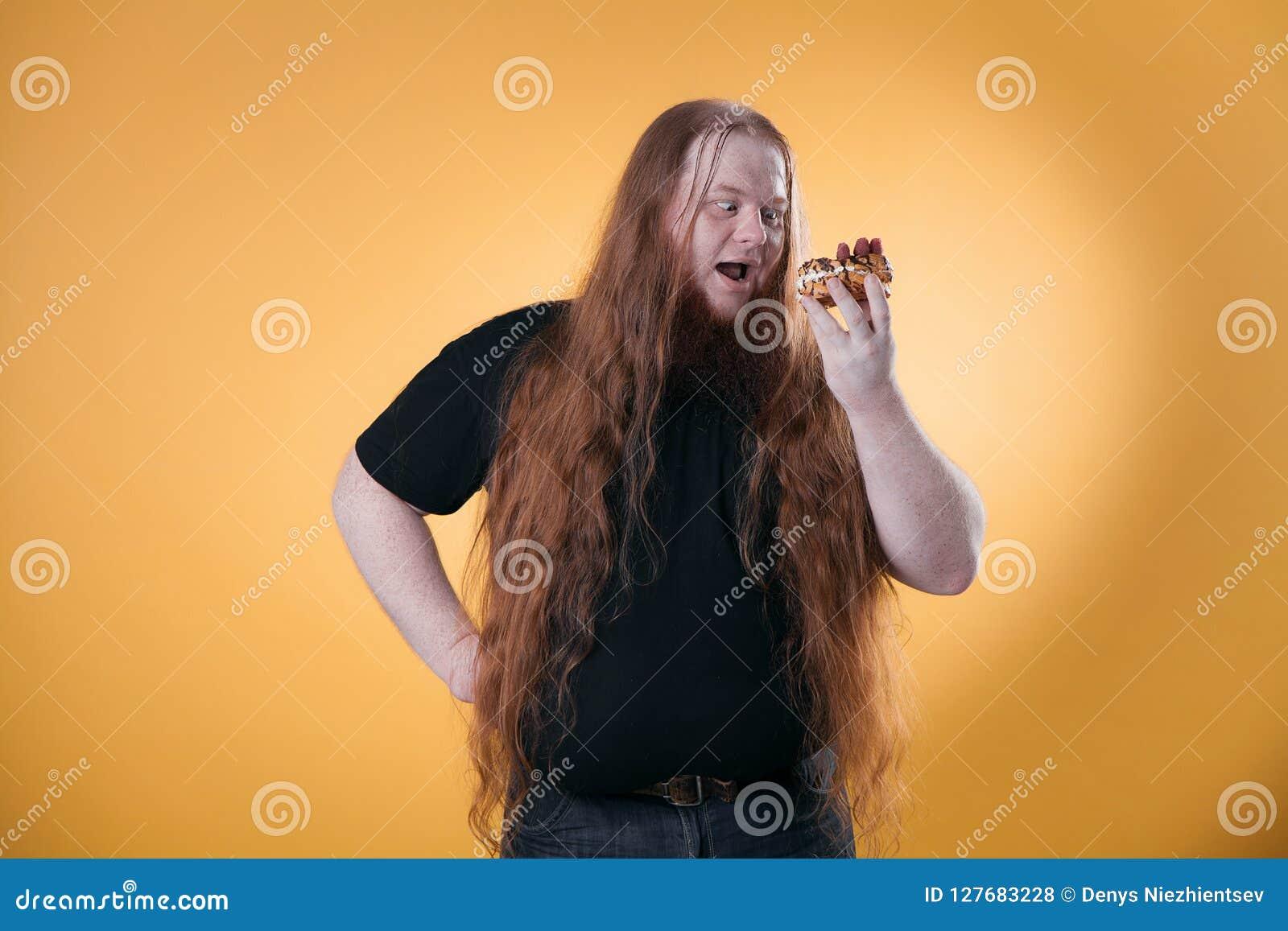 En stor fet man rymmer en söt kaka i hans hand
