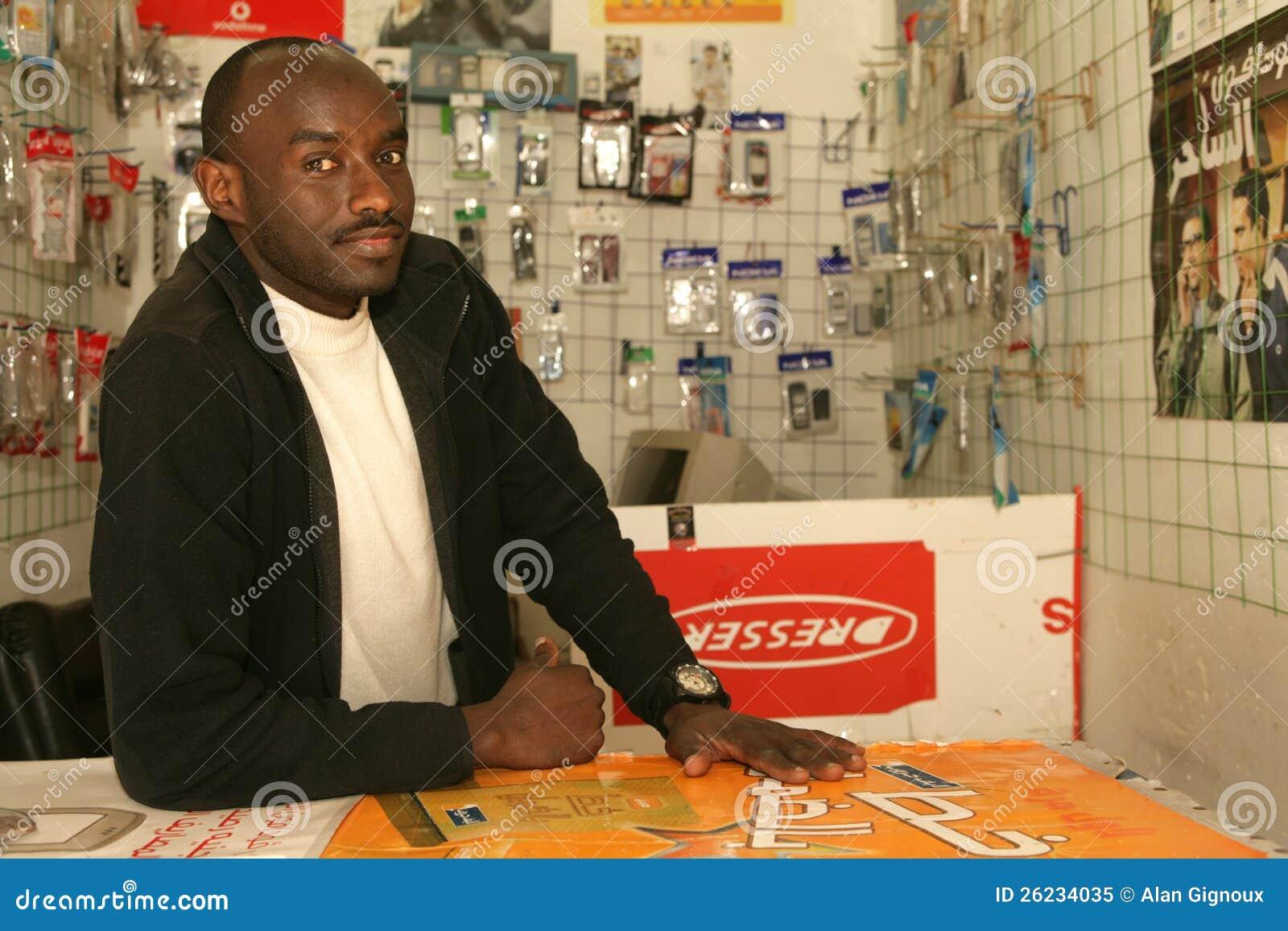 En sudanesisk flykting i hans mobiltelefon shoppar