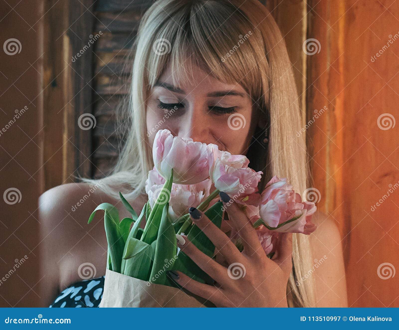 En suddig bild av en ung blond kvinna med blommor