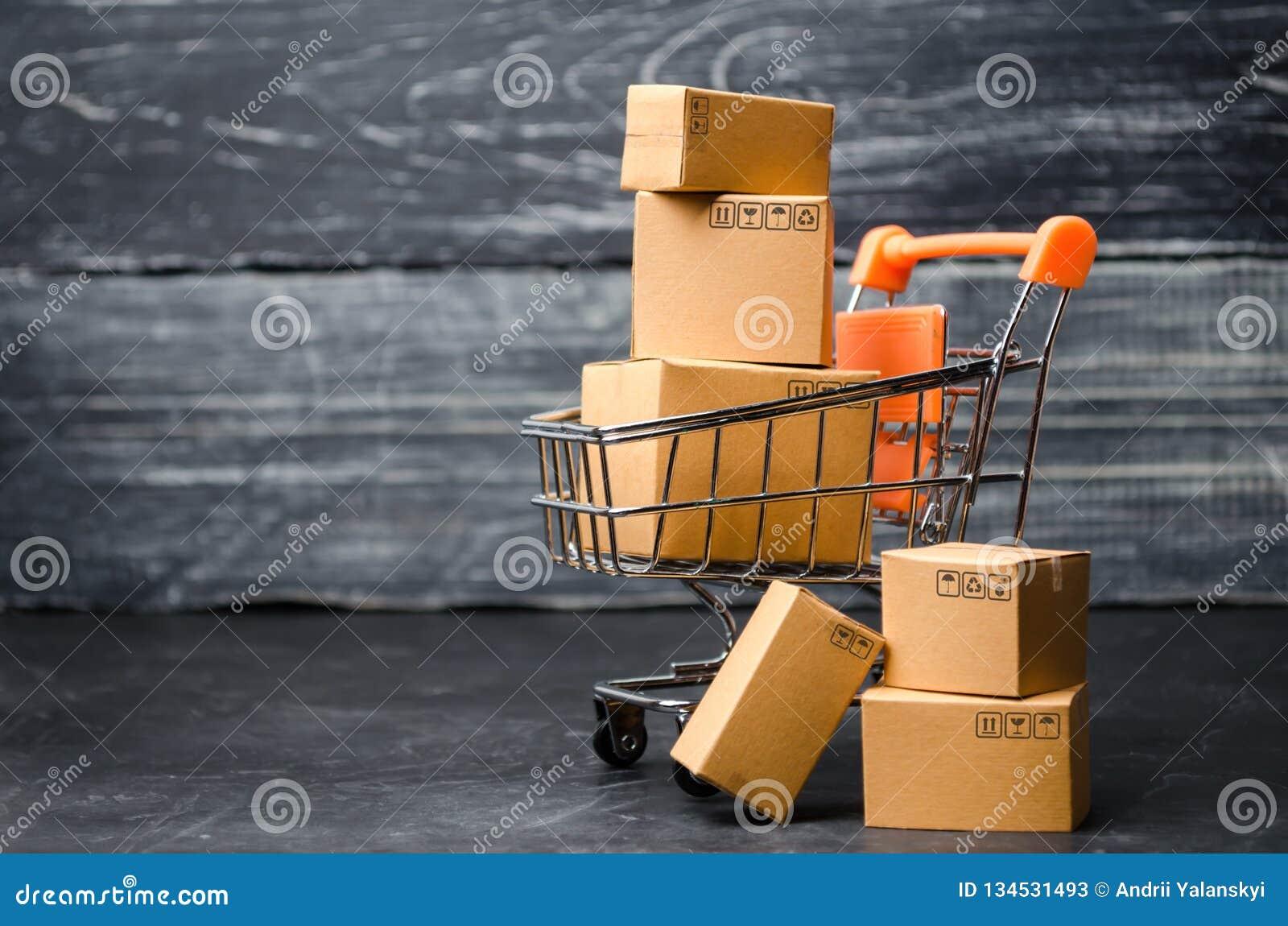 En supermarketvagn som laddas med kartonger Försäljningar av gods begrepp av handel och komrets, online-shopping högt leverans