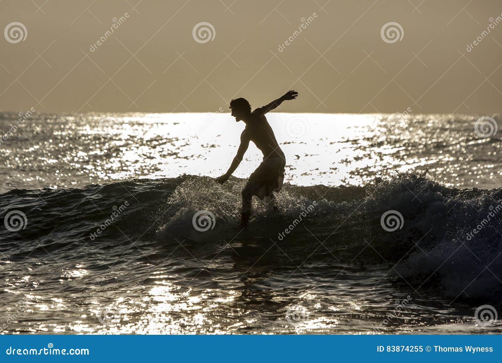 En surfare rider en våg på punktavbrottet på den Arugam fjärden i Sri Lanka på soluppgång