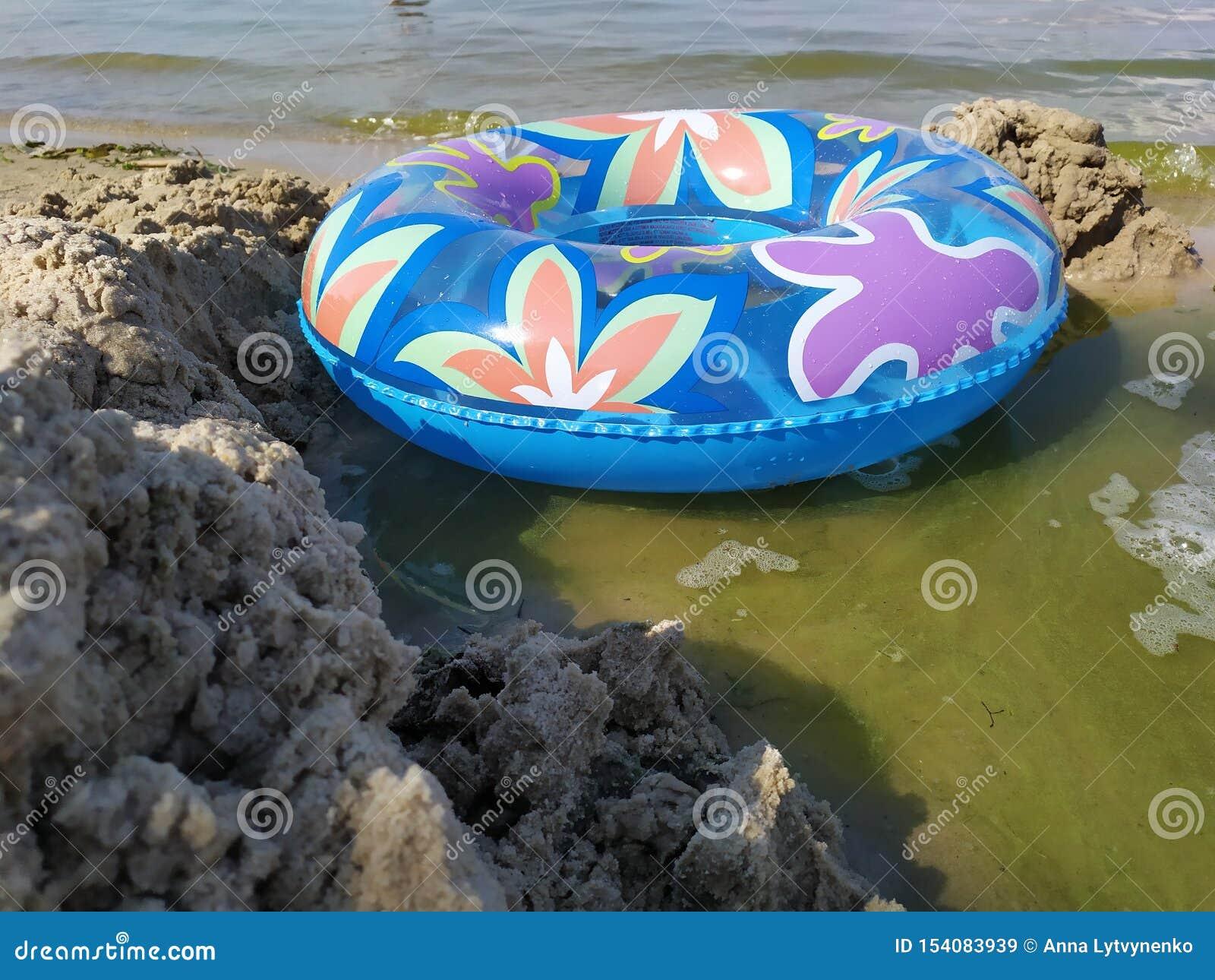 En sväva cirkel för barn ligger på den sandiga flodstranden nära vattnet