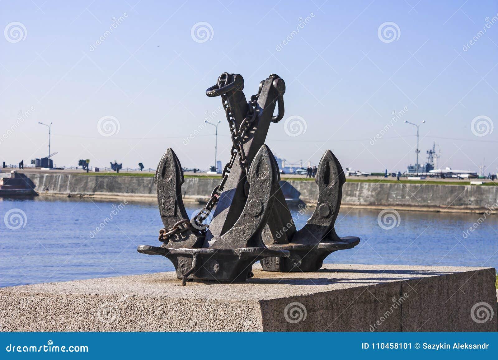 En symbolisk skulptur av ett ankare på granitpromenaden i hamnstaden av Kronstadt Rysk federation