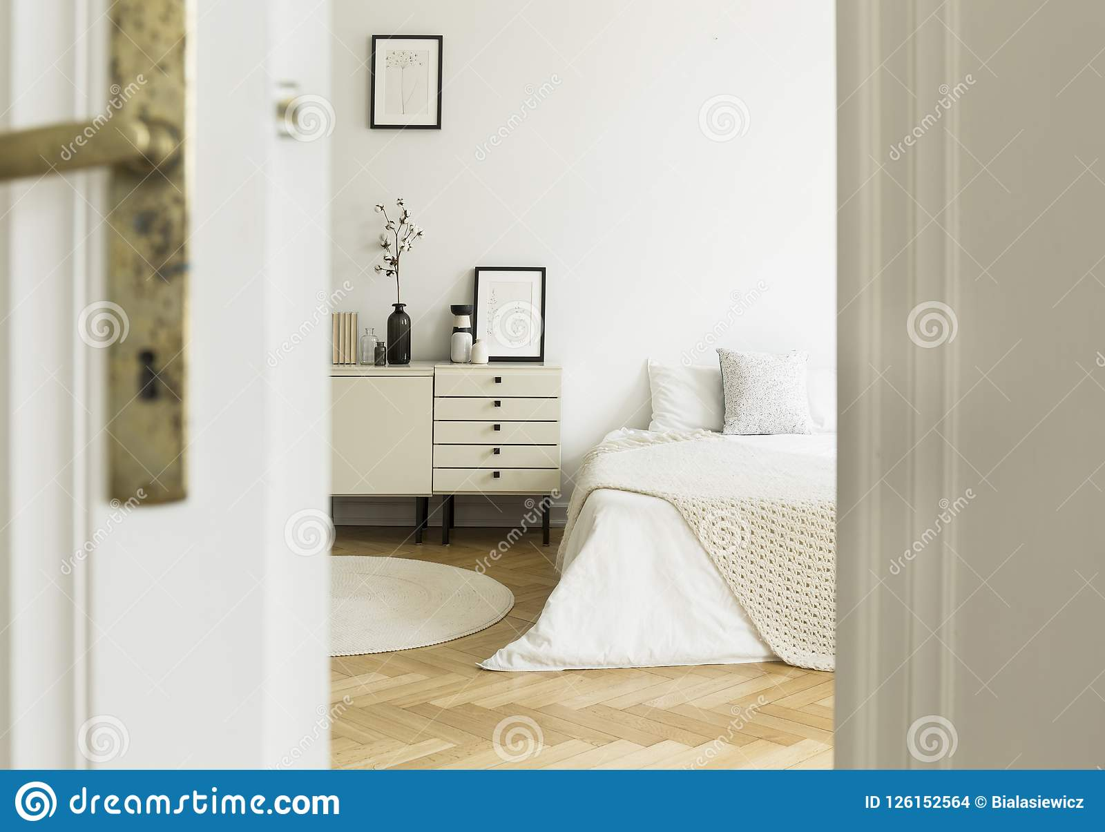 En titt till och med en dörr in i en monochromatic vit sovruminre med en säng och kabinetter som står på ett trägolv Verkligt fot