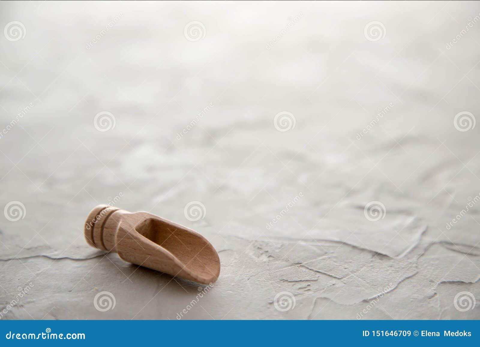 En tom träskopa för kryddor ligger på en konkret bakgrund placera text